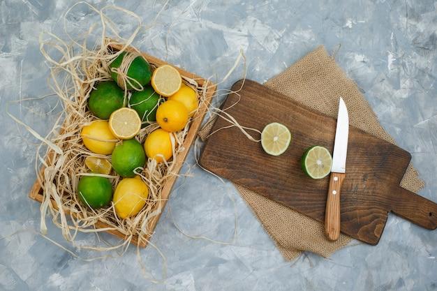 Niektóre limonki i cytryny z ręcznikiem kuchennym i nożem w desce do krojenia