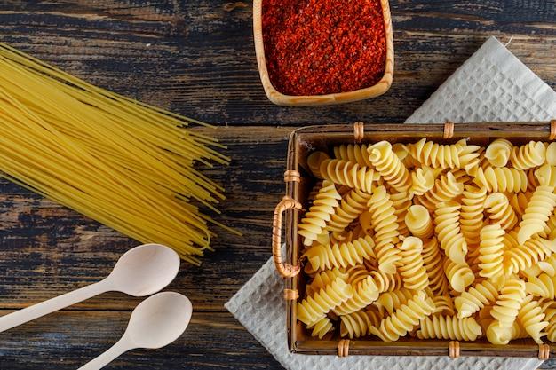 Niektóre makaronowy makaron z spaghetti, łyżki w tacy na drewnianym tle, odgórny widok.