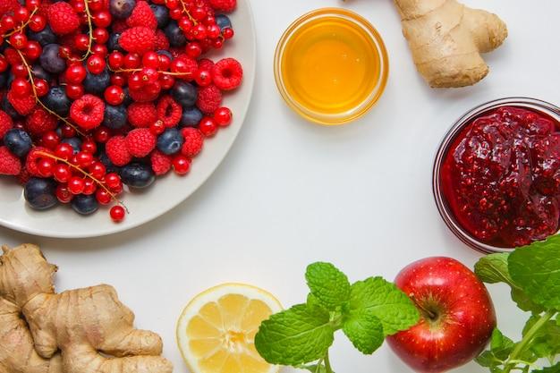 Niektóre maliny z liśćmi mięty, miód, jagody jagodowe, imbir, widok z góry.