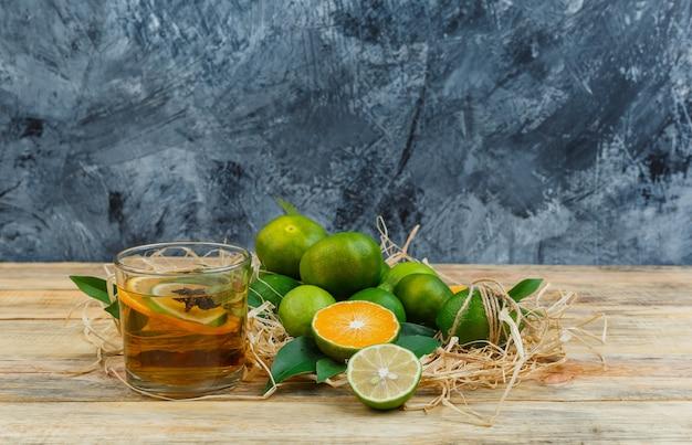 Niektóre mandarynki przy filiżance herbaty na niebieskim marmurze i drewnianej desce