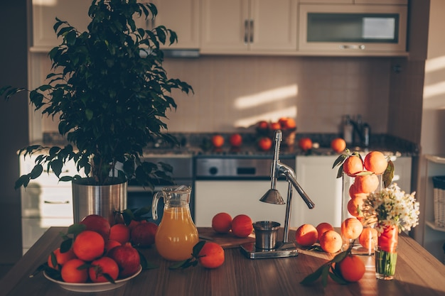 Niektóre owoce z sokowirówką i drzewa na stole i kuchni, widok z boku.