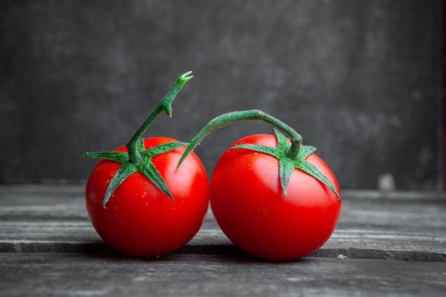Niektóre pomidory na ciemnym drewnianym i textured tle, boczny widok.