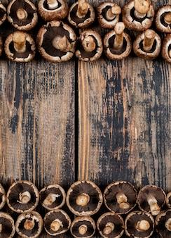 Niektóre przewrócone grzyby na górze i na dole, ciemny drewniany stół