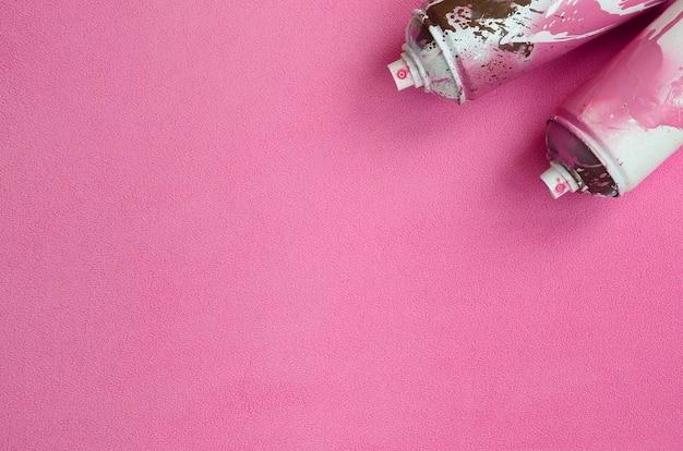 Niektóre puszki z aerozolem w kolorze różowym z kroplami farby leżą na kocu z miękkiej, futrzanej, jasnoróżowej tkaniny polarowej.
