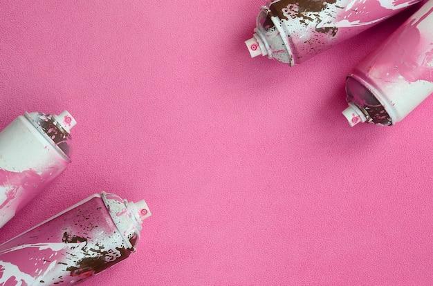 Niektóre puszki z aerozolem w kolorze różowym z kroplami farby leżą na kocu