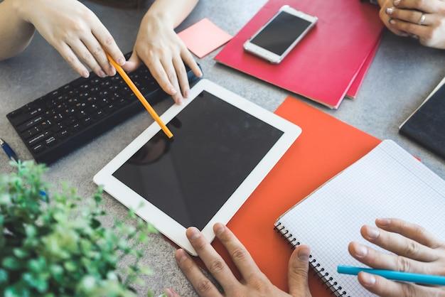Niektóre ręce w biurze pokazuje puste miejsce na komputerze typu tablet. wskazując ołówkiem i długopisem. czarny ekran makieta