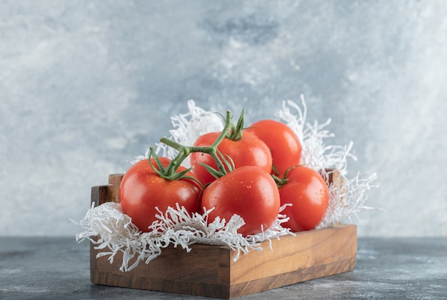 Niektóre soczyste pomidory na drewnianym koszu.