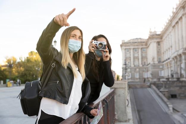 Niektóre wędrowne dziewczyny patrzą i fotografują część miasta. oboje mają maski na twarz. pojęcie turystyki i nowa normalność.