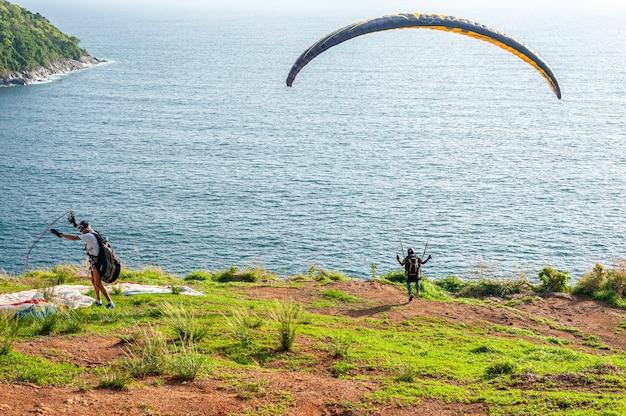Niektórzy ludzie z ekstremalnymi sportami spadochronowymi na wyspie o zachodzie słońca o zmierzchu