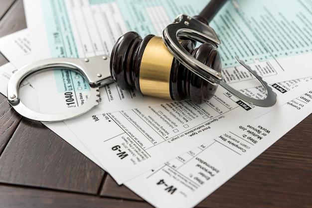 Nielegalne pojęcie formularz podatkowy usa z młotkiem i kajdankami. czas na biznes