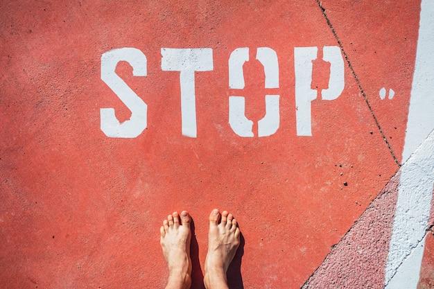 Nielegalny imigrant stoi boso przy znaku stop na ziemi.