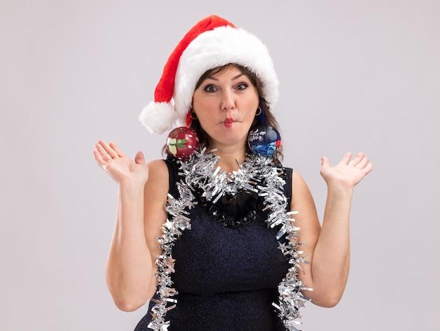 Niemądra kobieta w średnim wieku nosząca santa hat i blichtrową girlandę wokół szyi, patrząc na kamerę pokazującą puste ręce zaciskając usta z bombkami zwisającymi z jej uszu na białym tle