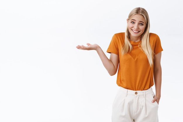 Niemądra, słodka kaukaska dziewczyna o blond włosach, nosi stylową pomarańczową koszulkę, spodnie, uśmiecha się, wzrusza ramionami i podnosi jedną rękę w niezrozumiałym geście, przepraszam, stoi skromnie na białym tle