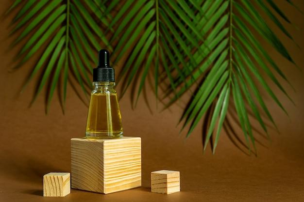Niemarkowa butelka z olejkiem eterycznym na postumencie. przezroczysty szklany pojemnik z zakraplaczem na tle tropikalnych liści. koncepcja kosmetologii i urody