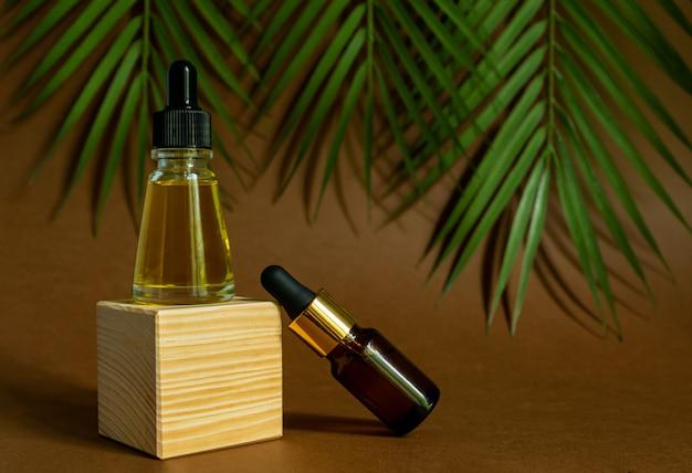 Niemarkowe butelki z olejkiem eterycznym na cokole. przezroczysty szklany pojemnik z zakraplaczem na tle tropikalnych liści. koncepcja kosmetologii i urody