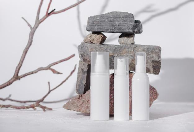 Niemarkowe medyczne produkty do pielęgnacji skóry, biała plastikowa butelka z dozownikiem i flakonami.