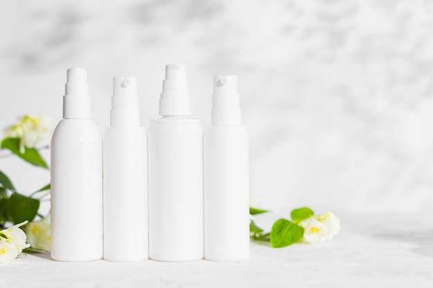 Niemarkowe plastikowe butelki produktów do pielęgnacji skóry z dozownikiem i flakonami