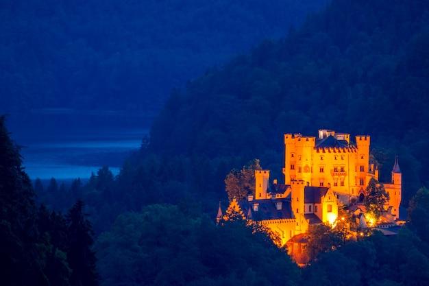 Niemcy. zalesione góry i jezioro. letnia noc. jasne oświetlenie starożytnego zamku
