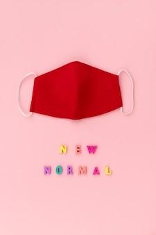 Niemedyczna maska maskująca twarz z napisem new normal