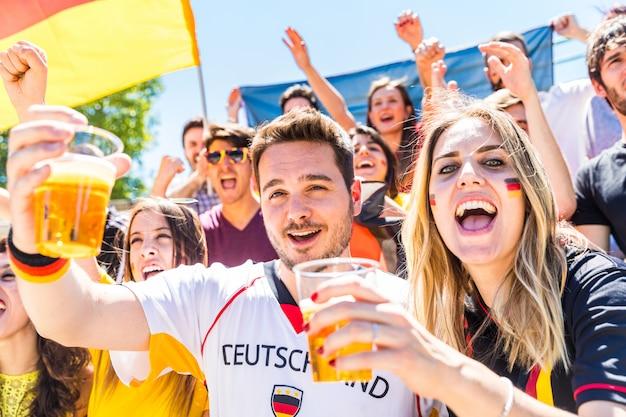 Niemieccy kibice świętujący na stadionie i pijący piwo