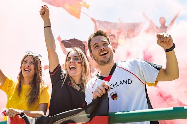 Niemieccy kibice świętujący na stadionie mecz piłki nożnej