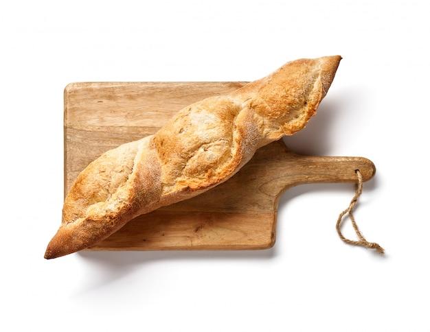 Niemiecka baguette na drewnianej desce odizolowywającej. widok z góry lub chleb francuski. piekarnia.