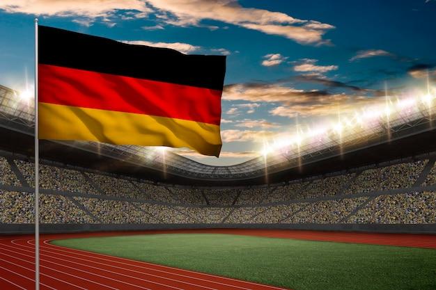 Niemiecka flaga przed stadionem lekkoatletycznym z kibicami.