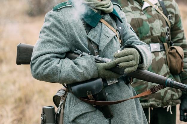 Niemiecki żołnierz z karabinem i papierosem w ręku