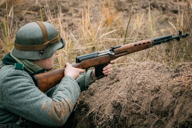 Niemiecki żołnierz z radzieckim karabinem w okopie
