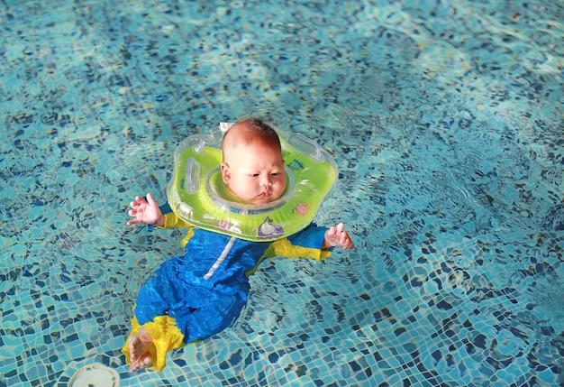 Niemowlę chłopca w pływanie garnitur pływające w basenie z bezpieczeństwem przez dziecko szyi płynie.
