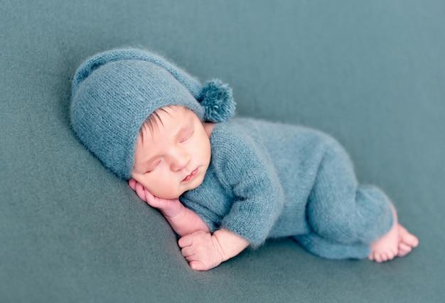 Niemowlę chłopiec śpi w wełniany kostium z bosymi stopami