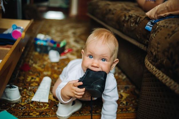 Niemowlę dziecko dziecko chłopiec sześć miesięcy bierze swój but w usta.