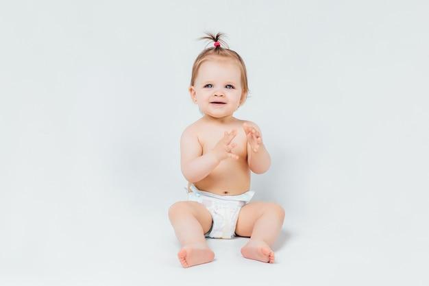 Niemowlę dziecko dziewczynka maluch raczkuje szczęśliwie patrząc prosto na białym tle na białej ścianie
