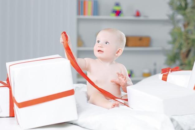 Niemowlę dziecko maluch dziecko siedzi w prezenty prezent na uroczystość. koncepcja boże narodzenie nowy rok.