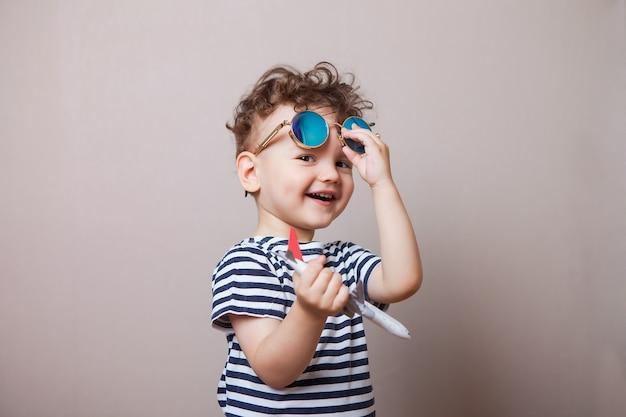 Niemowlę, dziecko z zabawkowym samolotem w dłoniach i okularami przeciwsłonecznymi. turysta