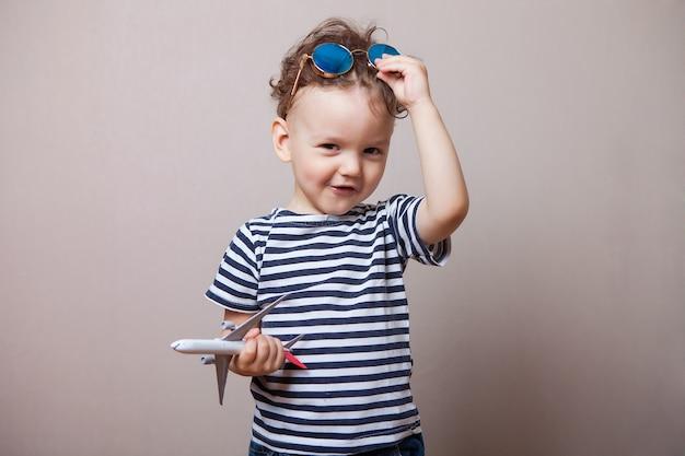 Niemowlę, dziecko z zabawkowym samolotem w dłoniach i okularami przeciwsłonecznymi.