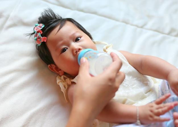 Niemowlę dziewczynka karmienia mleka z butelki matka strony.