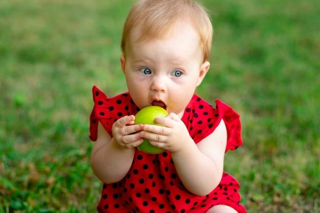 Niemowlę je zielone jabłko w czerwonym body na zielonej trawie latem, miejsce na tekst