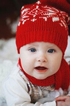 Niemowlę w czerwonej czapce z kulkami w noworocznym wnętrzu.