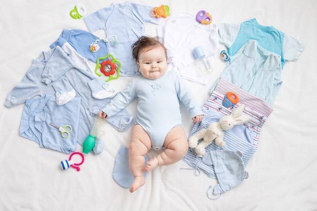 Niemowlę w niebieskiej sukience leży wśród dziecięcych akcesoriów i ubrań
