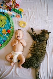 Niemowlę w pieluchach leży na łóżku obok ogromnego pręgowanego kota