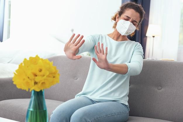 Niemożliwy zapach. młoda, kręcona kobieta źle się czuje, doświadczając nadwrażliwości na świeżo kwitnące wiosenne kwiaty, gdy nosząca maskę oddechowa nie pomaga jej