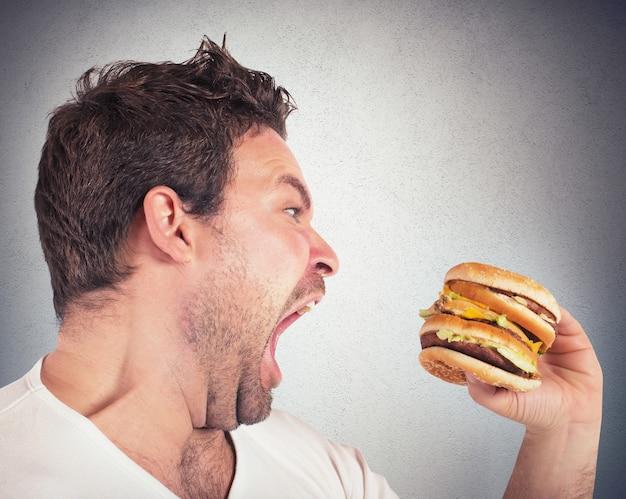 Nienasycony i głodny mężczyzna je kanapkę