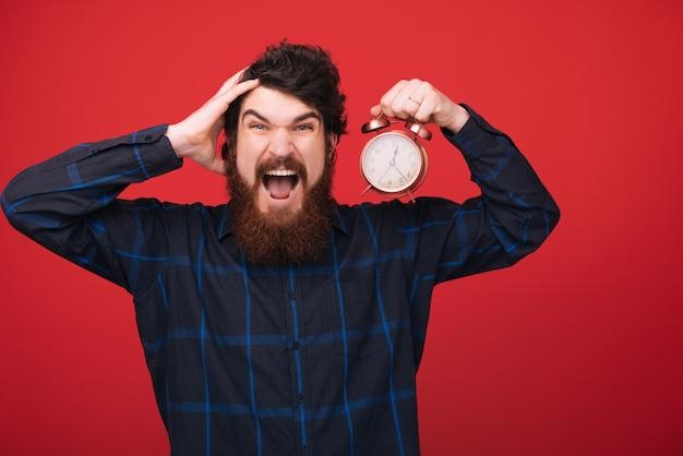 Nienawidzę spóźniać się. mężczyzna trzymać budzik w ręku. brodaty mężczyzna z zegarem na czerwonej ścianie