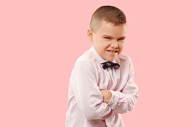 Nienawiść, wściekłość. emocjonalny zły nastolatek chłopiec na różowym tle studio. emocjonalna, młoda twarz. portret mężczyzny w połowie długości. ludzkie emocje, koncepcja wyrazu twarzy. modne kolory