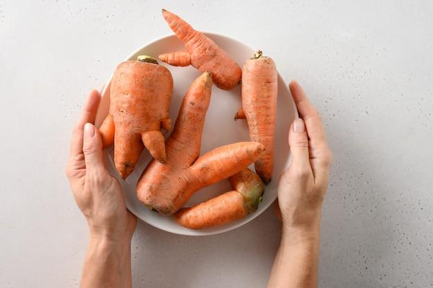 Nienormalne brzydkie organiczne marchewki na białym tle z naturalnymi warzywami