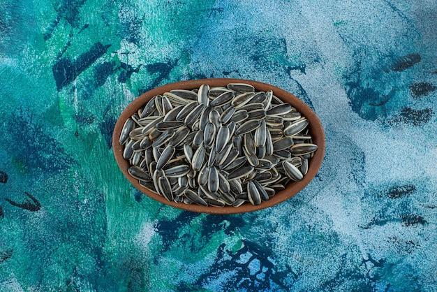 Nieobrane nasiona słonecznika w glinianej misce, na marmurowym stole.