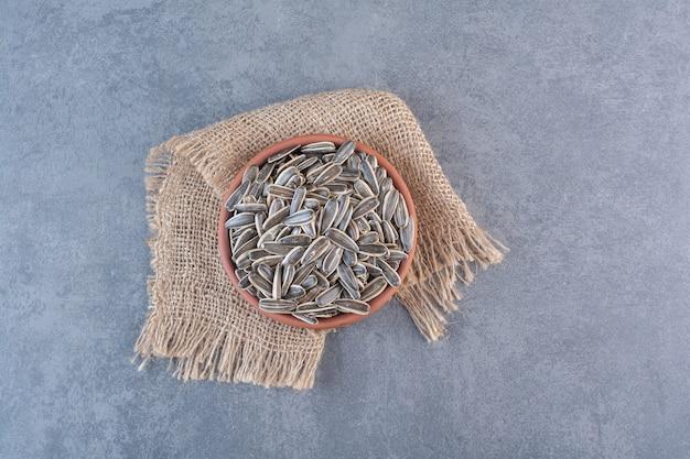 Nieobrane nasiona słonecznika w glinianym talerzu na fakturze, na marmurowej powierzchni
