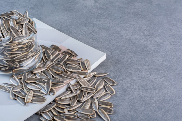 Nieobrane nasiona słonecznika w szkle na zeszycie, na marmurowej powierzchni