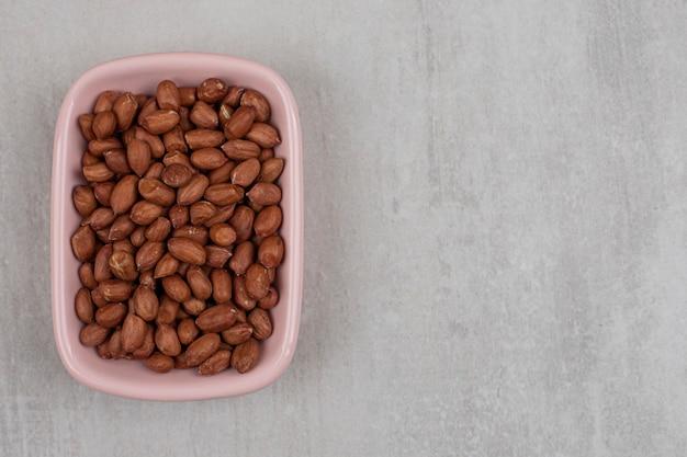 Nieobrane organiczne orzeszki ziemne w różowej misce.